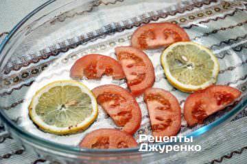 Форму для запікання трохи змастити олією. На дно укласти шматочки лимона, з якими маринувалися риба