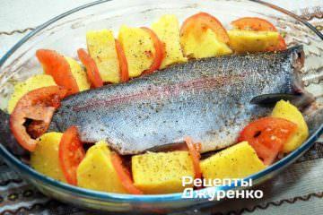 Навколо форелі викласти гарнір: шматочки печеної картоплі, упереміш з шматочками помідора