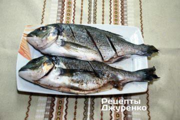 Випатрати рибу, видалить хребет, посипати спеціями і зробити неглибокі надрізи з боків