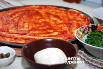 Смазать тесто томатным соусом