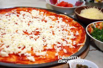 Моцареллу натерти на крупну тертку і розподілити по поверхні піци