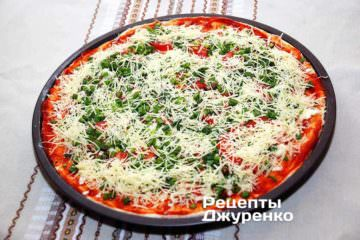 Посипати піцу тертим пармезаном. Побризкати оливковою олією