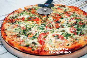 Готовую пиццу переложить на деревянную подложку и разрезать