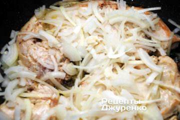 Засыпать филе нарезанным луком, убавить огонь