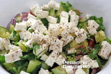 Поверх салата разложить нарезанный кубиками сыр фета