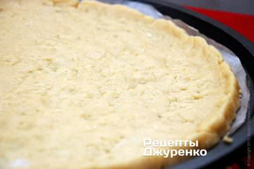 Положите на бумагу больший кусок теста и сухими руками растягивайте тесто в тонкий слой