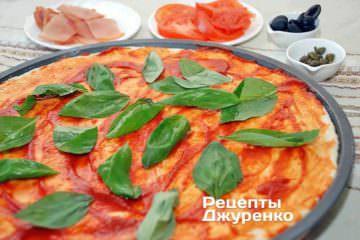 Смазать тесто томатным соусом и разложить базилик