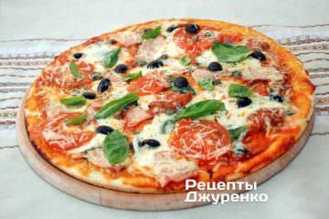 Готову піцу витягнути з духовки і покласти на дерев'яну підкладку для піци