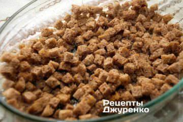 Влити в форму оливкову олію і розмазати їїо по дну. Висипати у форму підготовлений хліб і акуратно перемішати його
