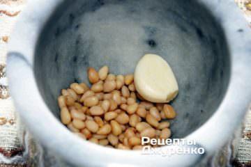 У ступці змішати 2/3 кедрових горішків, 1 зубчик часнику і дрібку солі