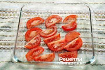 Форму для запікання змастити оливковою олією і розкласти по дну нарізаний тонкими скибочками помідор