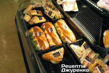 Величезний свіжий батон з ковбасою, помідорами, цибулею, маринованими огірками, зеленим салатом, соусом