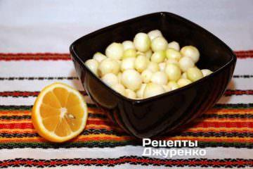 Очищенный лук сложить в неокисляемую посуду, полить соком лимона, добавить 1 ч.л. соли , залить холодной водой и поставить холодильник