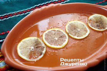 Глиняний деко - плато, змастити оливковою олією. По центру викласти в ряд кілька дуже тонких кружечків лимона
