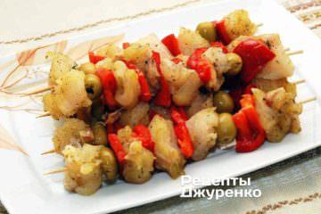 Нанизать, чередуя, кусочки рыбы, перец и оливки на деревянные шпажки