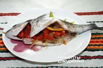 Заполнить внутреннюю полость и голову рыбы подготовленным луком и помидором