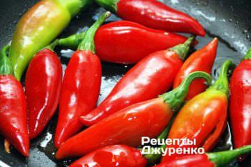 На сковородке разогреть оставшееся оливковое масло и обжарить на нем очищенный и подготовленный перец