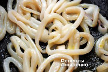 На сковорідці розігріти всю оливкову олію і обсмажити колечка кальмарів на сильному вогні, постійно помішуючи