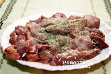Посолити і поперчити шматочки печінки за смаком. Бажано додати 1-2 щіпки ароматних трав: кріп, базилік, чабер