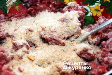 Небольшими порциями добавлять в фарш крошки и вымешивать