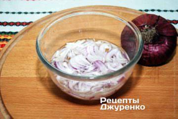 Луковицу очистить, разрезать вдоль пополам, нарезать на очень тонкие пластинки. Далее сложить в миску залить холодной водой