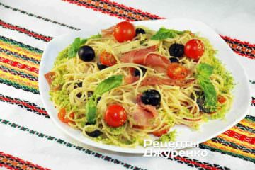 Разложит спагетти с ветчиной, помидорами и оливками на тарелки