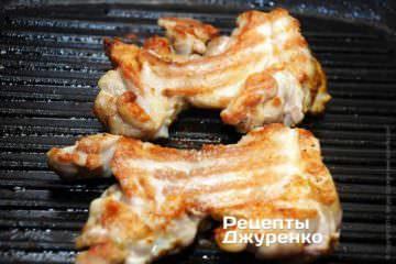 За допомогою лопатки перевернути курячі стегна і смажити ще 4 хвилини