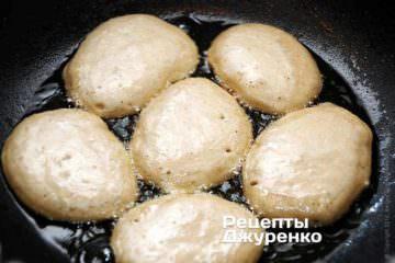 Звичайною столовою ложкою набирати рідке тісто і викладати його в розігріту олію, формуючи овальні оладки