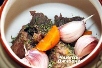 Мясо и отваренную морковь переложить в горшочки, добавив неочищенные зубчики чеснока. Добавить 1-2 щепотки сушеного чабера