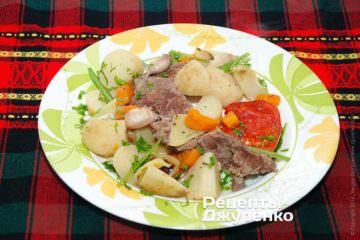 Во время трапезы выкладывать ложкой мясо с овощами и молодым картофелем на тарелку, посыпая блюдо мелко нарезанной петрушкой