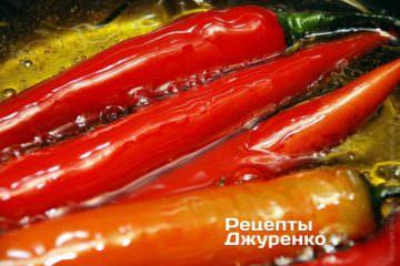 Кастрюлю с маслом поставить на огонь. Бросить в масло перец «чили». Довести до кипения и убавить огонь до минимума. Тушить перец в масле 10 минут.