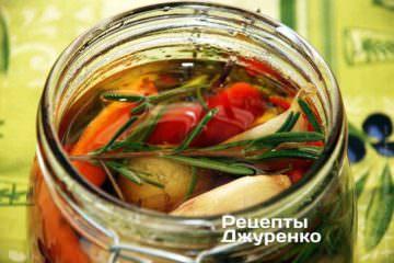 Перец переложить в банку с чесноком. Если перец достаточно длинный, его можно согнуть или сложить пополам. Вылить в банку все ароматизированное оливковое масло