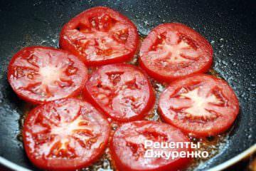 Помидор разрезать на кружочки толщиной 3-4 мм. Обжарить помидор на масле по 1 минуте с каждой стороны