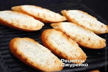 Багет нарезать на ломтики толщиной 12-15 мм сильно наискосок. Поджарить куски хлеба с двух сторон
