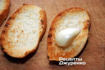Очистить зубчик чеснока и натереть им поджаренный хлеб с одной стороны. Затем смазать натертую сторону небольшим количеством свежего оливкового масла