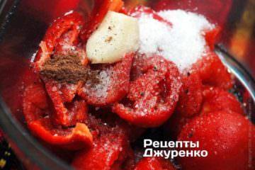 Мякоть томатов сложить в измельчитель. Добавить очищенный от семян и корешка красный сладкий перец, очищенный зубчик чеснока. Добавить щепотку соли, молотый мускатный орех и одну неполную ложку сахара