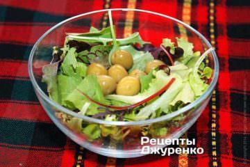 Выложить чистые и сухие листья выбранного салата в миску. Добавить зеленые оливки