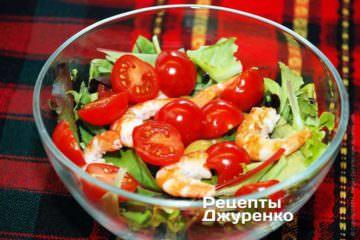 Помидоры черри разрезать пополам и добавить в салат. Выложить в салат подготовленные креветки