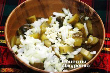 Добавить мелко нарезанные лук и чеснок к огурцам
