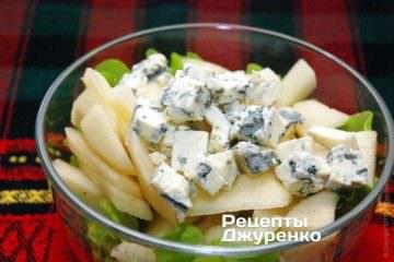 Сыр с голубой плесенью нарезать ножом на кубики и добавить в салат с грушей