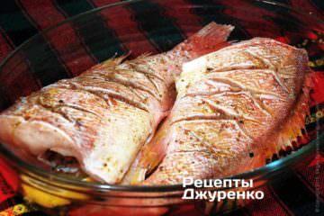 На скибочки лимона укласти тушки окунів. Обмазати рибу оливковою олією, досить 1 ст.л.