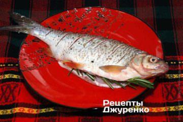 Сделать 5-7 неглубоких надрезов с боков тушки плотвы. По вкусу посолить рыбу и поперчить