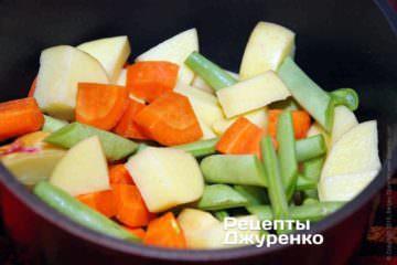 В небольшую кастрюлю сложить нарезанную морковку, картошку и спаржевую фасоль. Залить холодной водой вровень с овощами