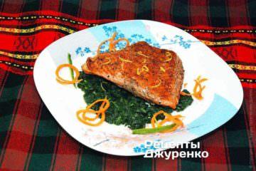 На большую тарелку выложить зеленый соус из шпината, распределив его по всей тарелке. Поверх соуса выложить филе рыбы на гриле