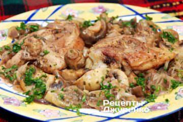 Курица с шампиньонами выкладывается на тарелки и поливается образовавшимся соусом