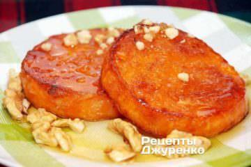 Готовую жареную тыкву выложить на тарелку и полить медом. Посыпать поджаренными орехами