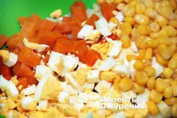 Добавить к овощам нарезанные яйца и консервированную кукурузу
