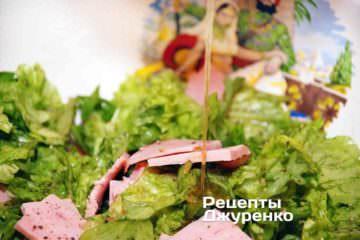 Полити заправкою салатні листя і перемішати
