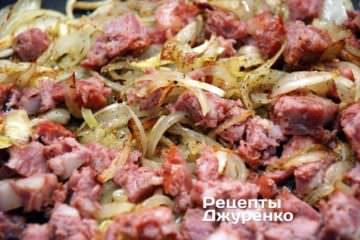 Добавить к обжаренному луку нарезанную колбасу