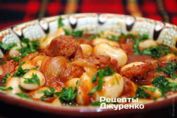 Викласти квасоля з ковбасою на тарілки